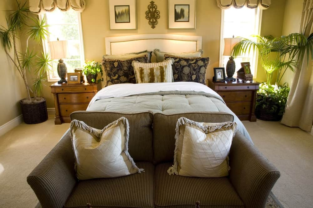 This primary bedroom boasts a white leather bed and a striped couch topped with tasseled pillows. It has wooden nightstands and framed windows dressed in lovely beige valances.