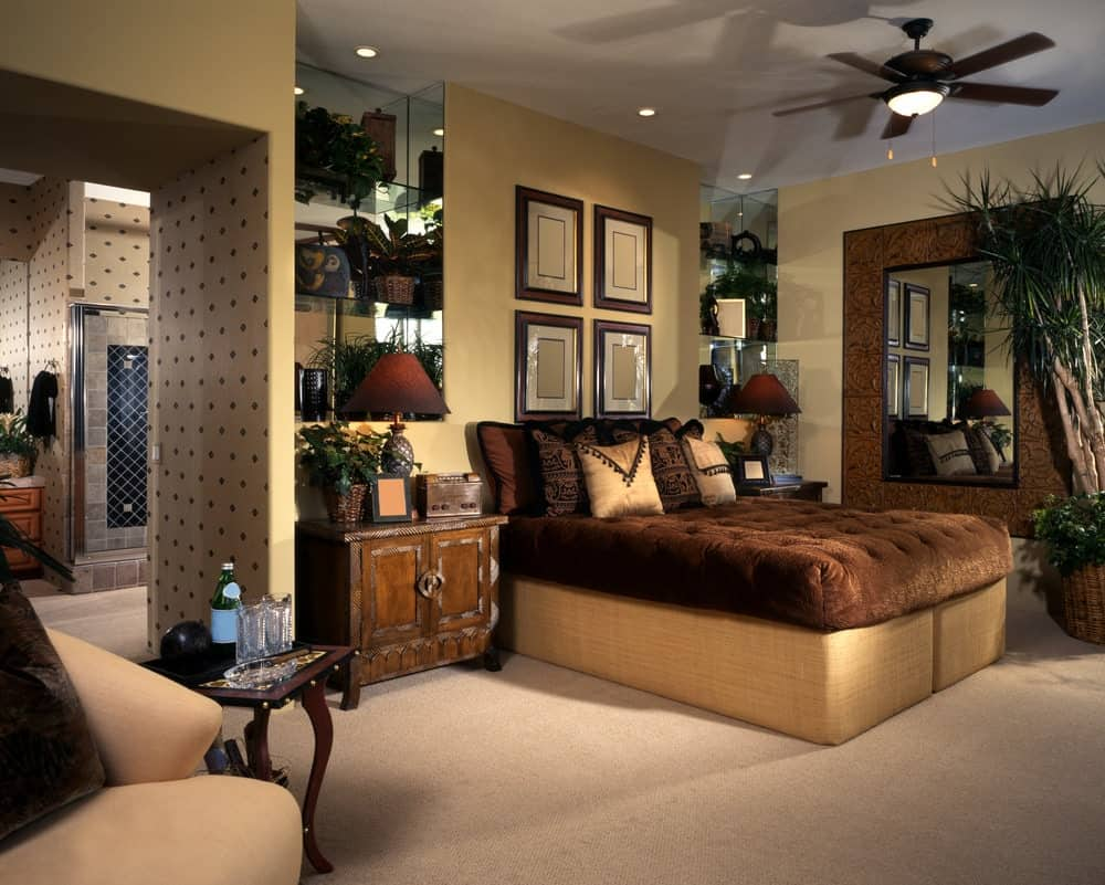 Wooden framed wall arts hang above the brown tufted bed that's illuminated by a flush light integrated to the ceiling fan. This room has wooden nightstands and a large ornate mirror mounted on the beige wall.