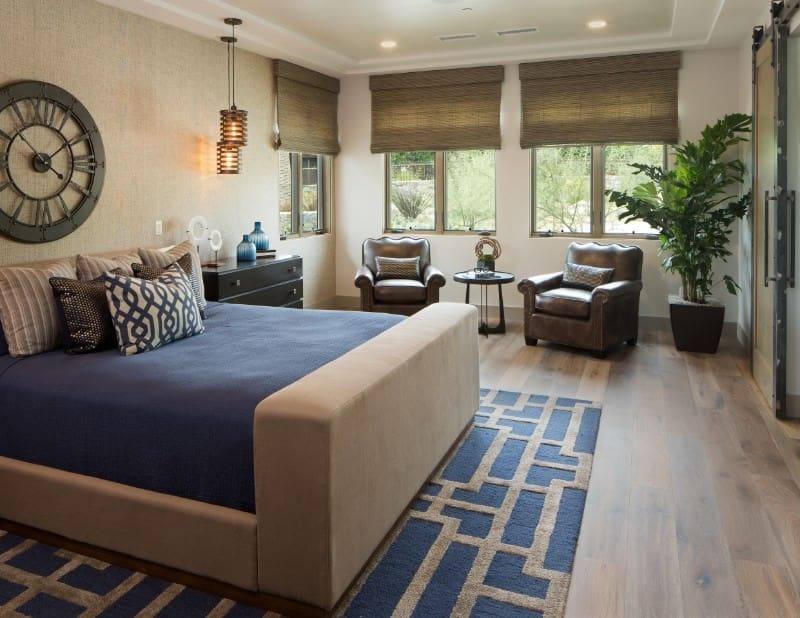 Stylish pendant lights hang over the black nightstand in this primary bedroom with a seating area and a beige upholstered bed on an eye-catching blue rug topped with a round wall clock.