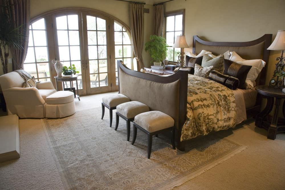Tropical primary bedroom features a white skirted lounge chair and upholstered bed with cushioned stools on its end that sit on a vintage area rug.