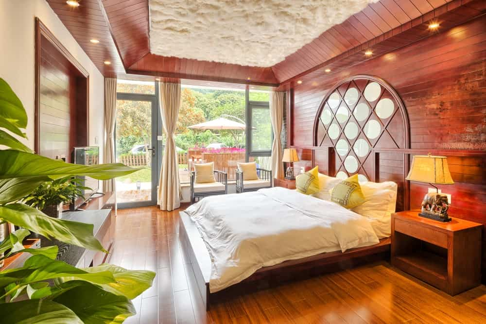 Warm bedroom with rich hardwood flooring and textured tray ceiling surrounded by recessed lights. It includes gray round back chairs and a cozy bed in between wooden nightstands topped with elephant table lamps.