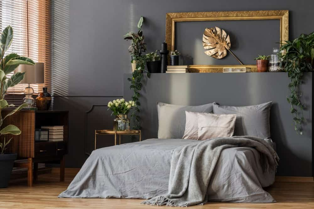 This primary bedroom is decorated with potted plants and a lovely leaf wall art framed in ornate gold. It is mounted above the platform bed that's dressed in gray bedding.