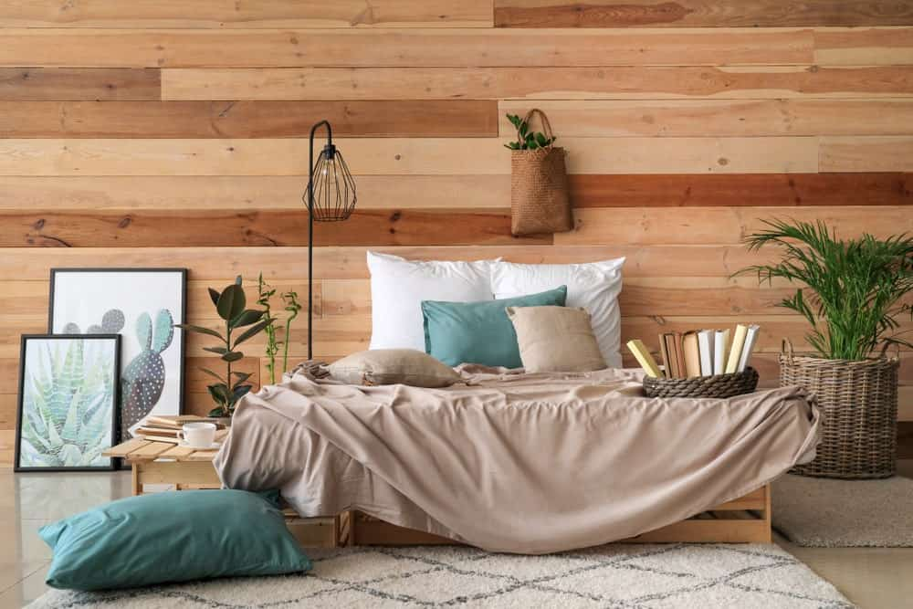 This primary bedroom features succulent artworks and a cozy bed lighted by a black industrial floor lamp. It has a wood paneled wall and tiled flooring topped by taupe rugs.