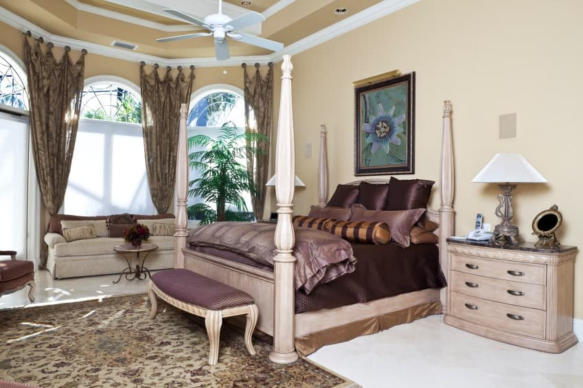 Elegant primary bedroom showcases a wooden four poster bed and a beige skirted sofa by the arched windows dressed in tropical curtains. It includes floral wall art and a white fan that hung from the tray ceiling.