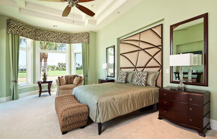 Zebra print valance matches the throw pillows in this mint green bedroom boasting a beige skirted armchair and a gorgeous bed with custom headboard flanked by wooden nightstands and mirrors.
