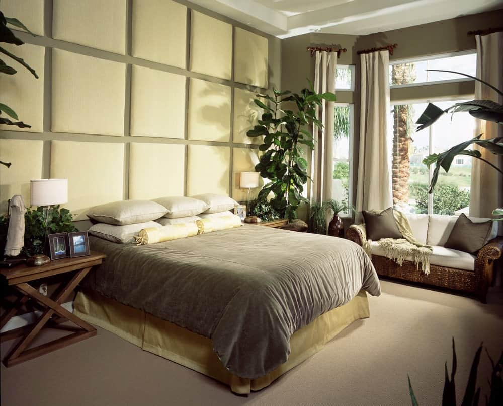 A rattan sofa topped with white sectional cushions faces the skirted bed in this primary bedroom with a tufted accent wall and glass paneled windows covered in gray draperies.