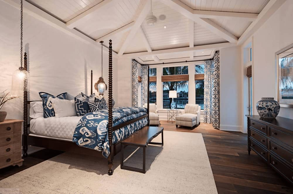 An oriental ceramic vase sits on the dark wood dresser in this white bedroom with striped armchairs and a four poster bed in between wooden nightstands lighted by glass pendants.