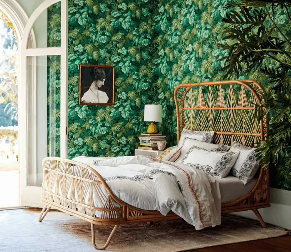 Clad in foliage wallpaper, this bedroom showcases a lovely portrait and wicker bed that sits on a beige area rug over rich hardwood flooring.