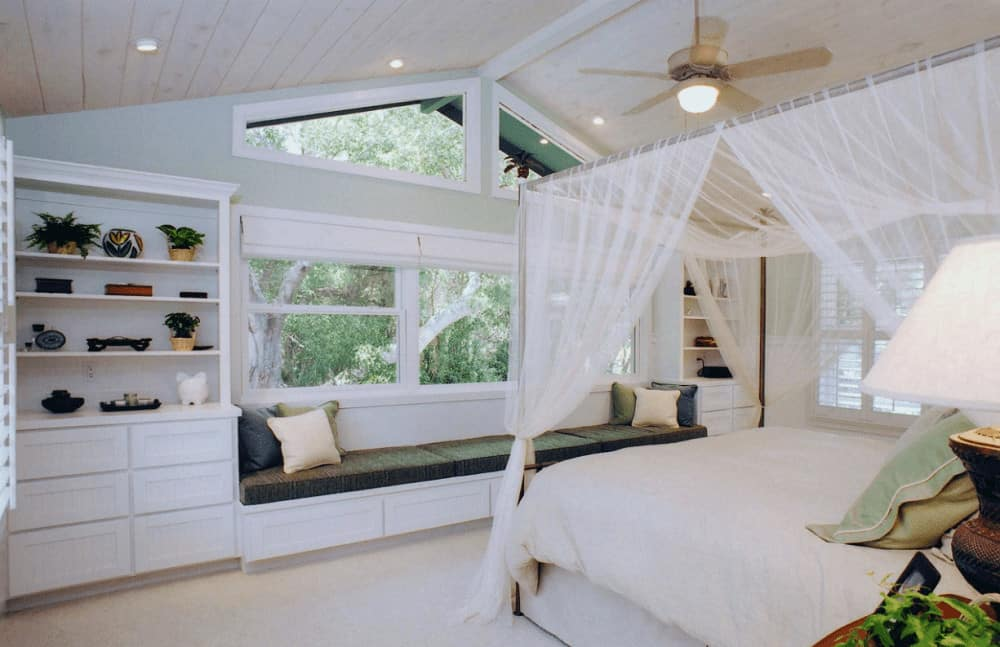 Airy bedroom with carpet flooring and cathedral ceiling mounted with recessed lights and fan. It has a canopy bed and a window seat nook placed in between built-in shelving.