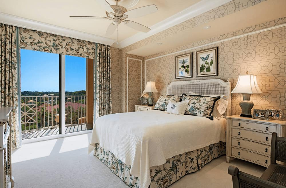 Classic primary bedroom boasts lovely wall arts and a white wooden bed flanked by nightstands and table lamps. It has full height glazing covered in floral drapes and valance that match the bed skirt and pillows.