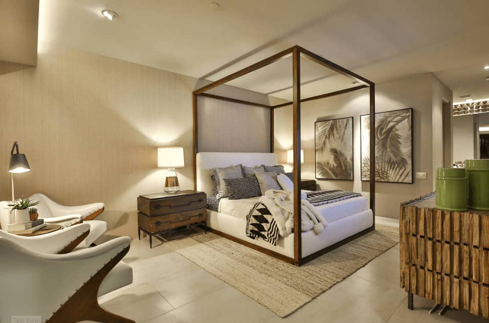 A wooden canopy bed sits on a jute rug in this primary bedroom with stylish seats and rustic nightstands topped with glass table lamps.