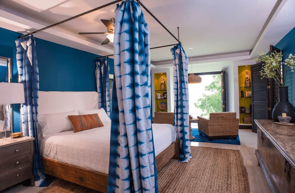 Blue bedroom offers inset wall niches fitted with glass shelves along with a cool canopy bed that sits on a jute rug. It is accompanied by wooden nightstands and wicker chairs illuminated by a dome pendant light.