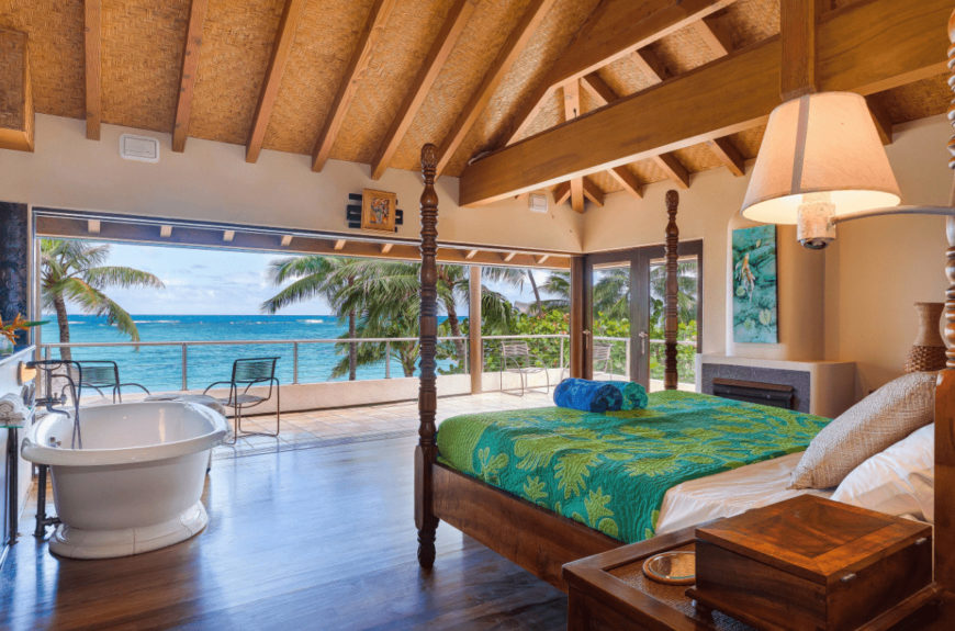 Cozy bedroom overlooking the stunning beach features a four poster bed wrapped in a beautiful tropical quilt along with a freestanding tub on the side over hardwood flooring.