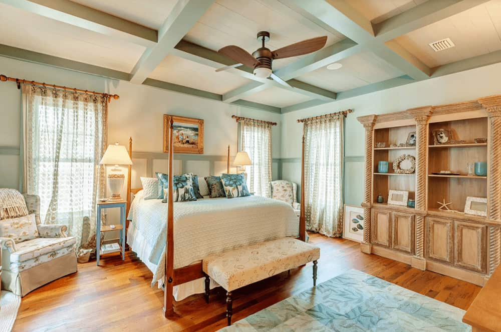 A lovely framed photo hangs above the four poster bed in this tropical bedroom boasting wooden shelving and blue floral armchairs that sit on rich hardwood flooring.