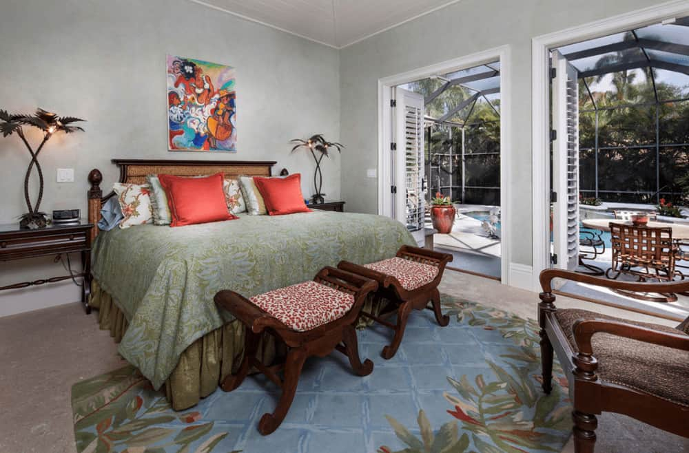 This primary bedroom features a colorful artwork and coconut tree lamps that sit on the dark wood nightstands. It includes a skirted bed and cushioned stools over a tropical area rug.