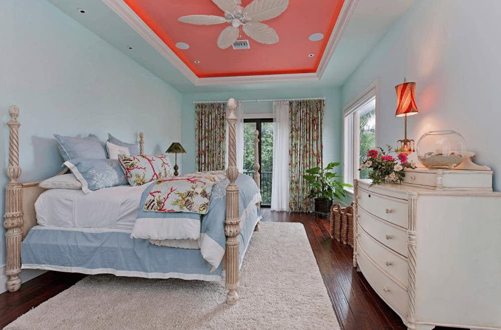A white ceiling fan with leaf blades is mounted on the coral tray ceiling in this charming bedroom with a classy four poster bed and drawer chest topped with a fishbowl and lovely table lamp.