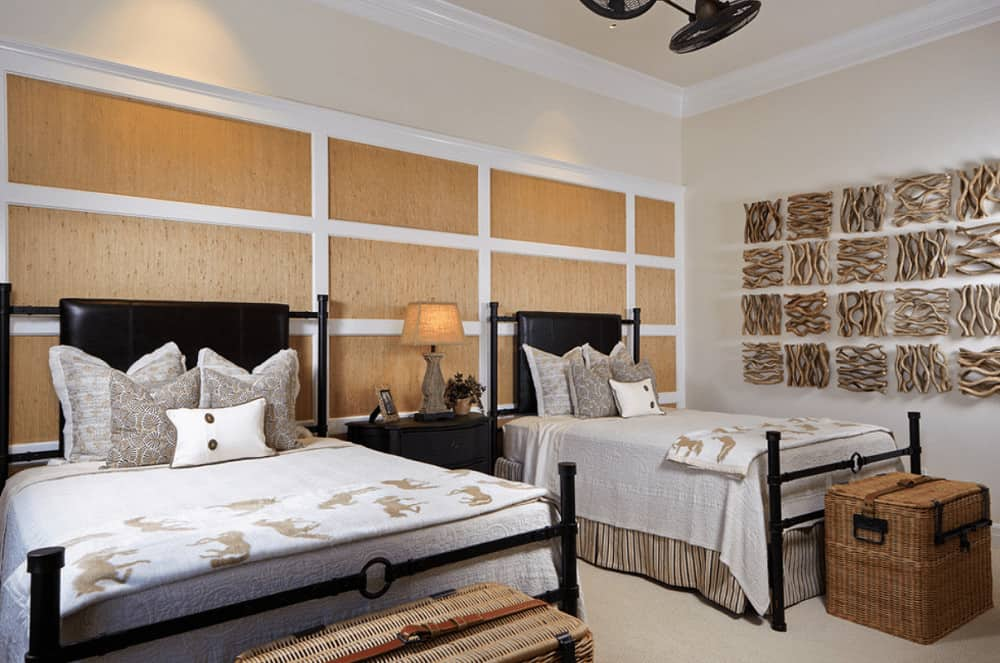 Shared bedroom designed with wood paneled walls and unique wood wall arts mounted across the black beds accompanied by a nightstand and wicker storage baskets.