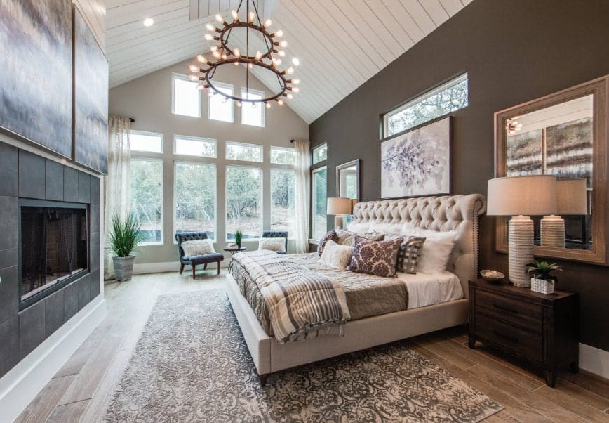 Large primary bedroom featuring a tall ceiling and hardwood flooring. The room boasts a large luxurious bed along with a large fireplace.