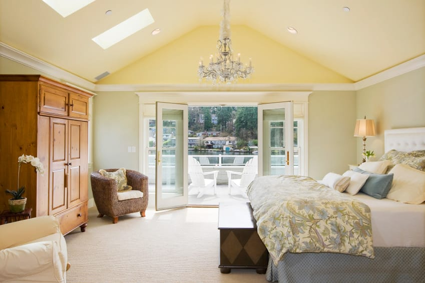 Spacious primary bedroom featuring a vaulted ceiling with skylights and carpet flooring. The room has a large elegant bed lighted by table lamps and a gorgeous chandelier.