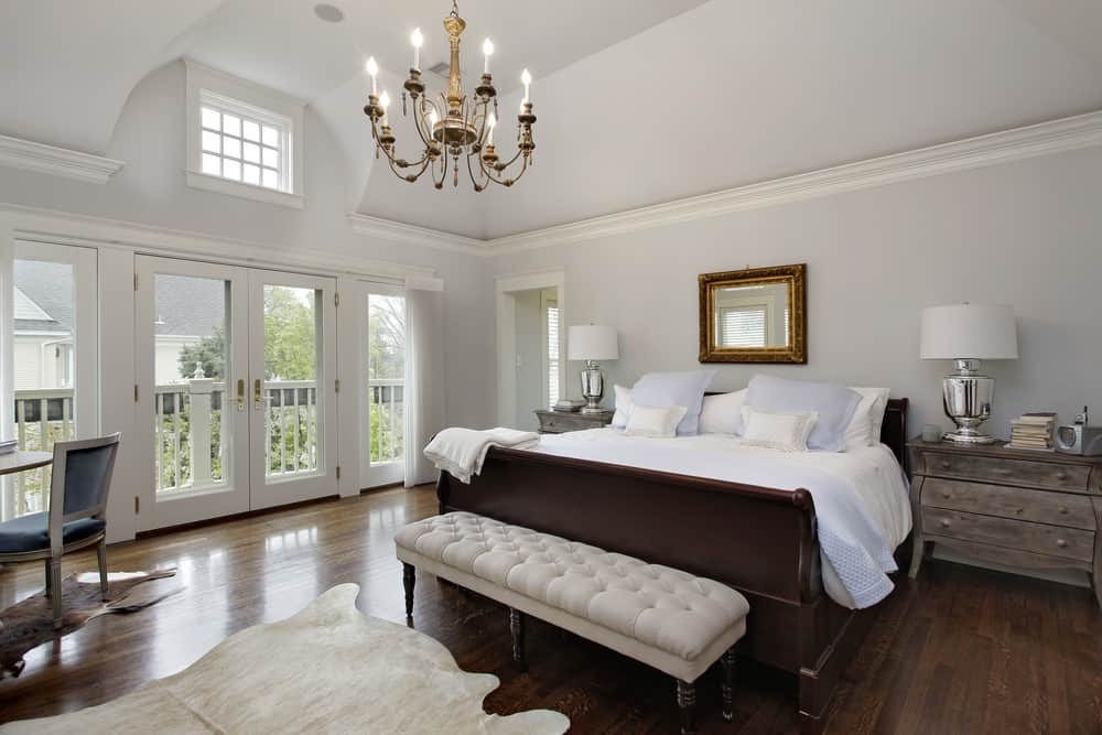 Large primary bedroom featuring light gray walls along with hardwood flooring. The room has a large bed with rustic bedside tables on both sides. The room is lighted by a gorgeous chandelier.