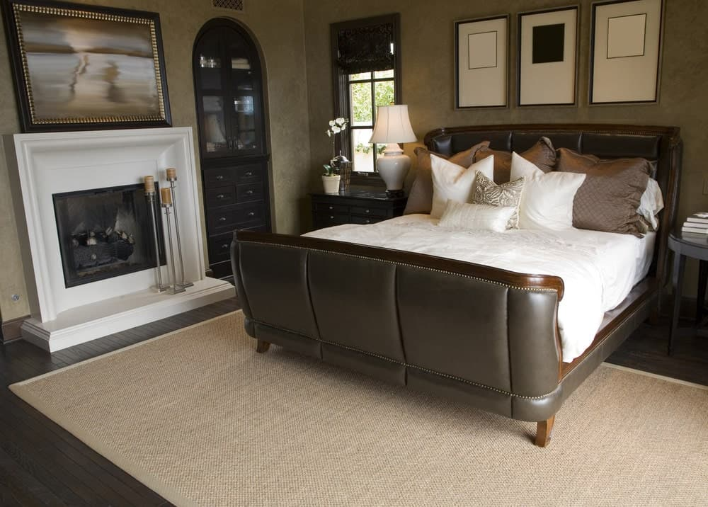 This bedroom offers a white fireplace and leather wingback bed with framed wall arts on top. It includes a dark wood nightstand and a jute rug that lays on the wide plank flooring.