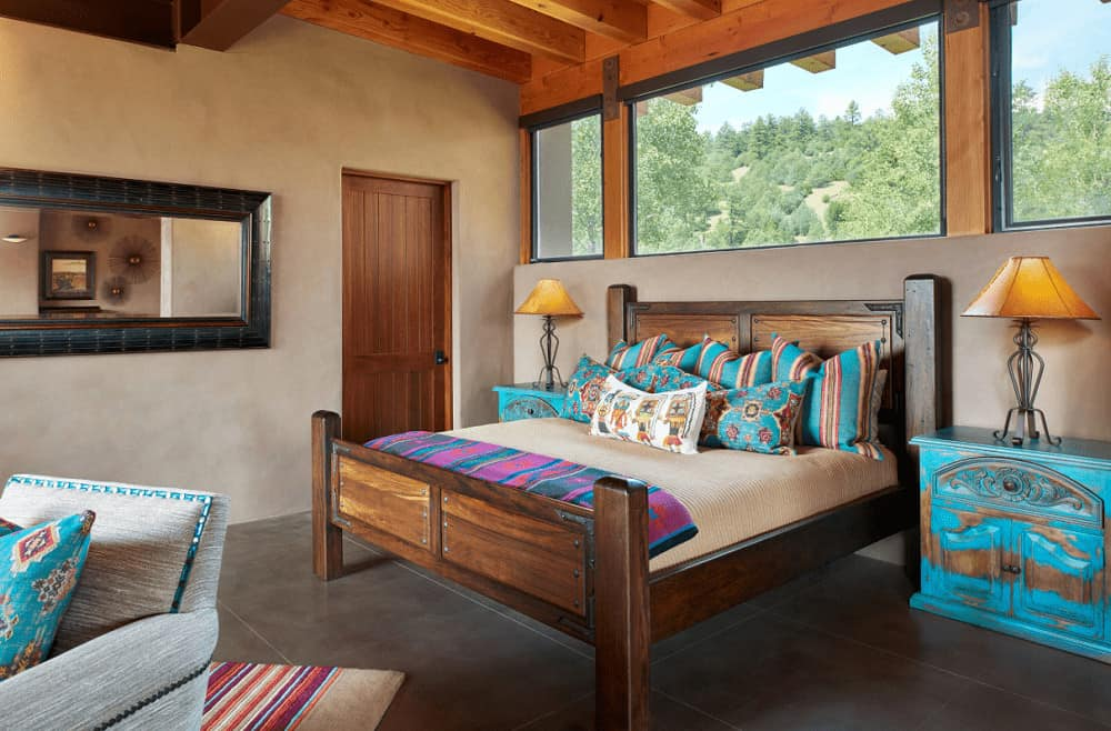This primary bedroom features a wooden bed and distressed blue nightstands topped with metal table lamps. It has tiled flooring and glass paneled windows overlooking the lush greenery.
