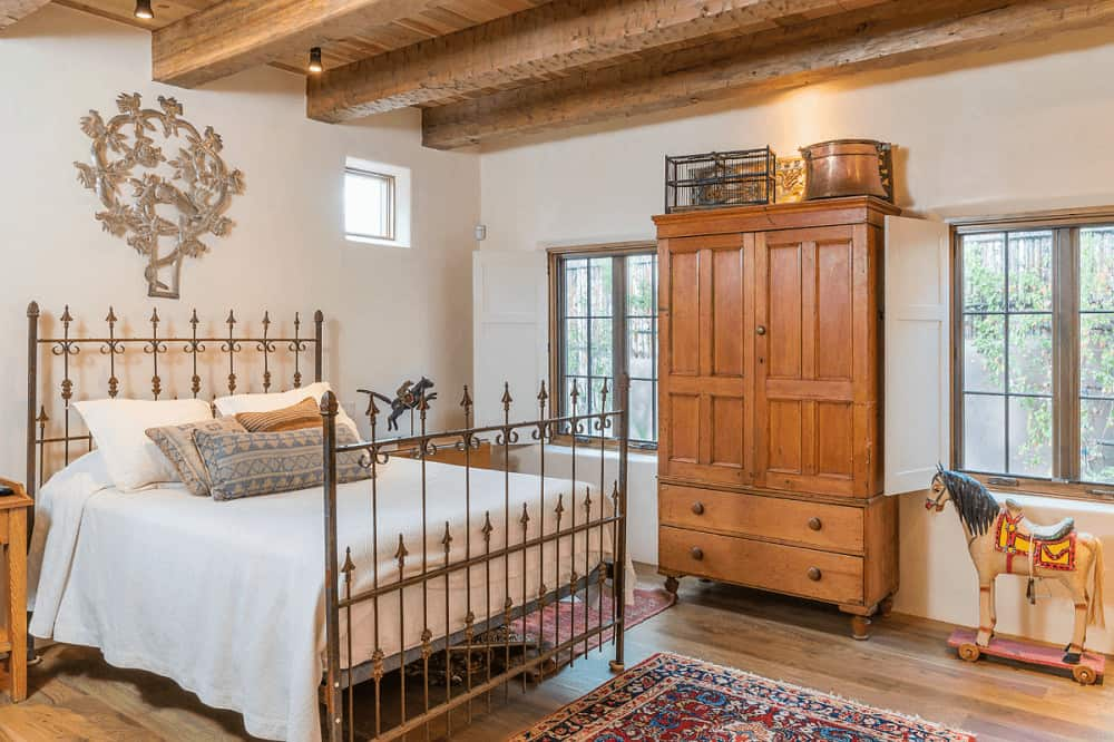 An ornate chrome wall art accentuates the metal bed in this primary bedroom with hardwood flooring and wood beam ceiling mounted with black track lights.