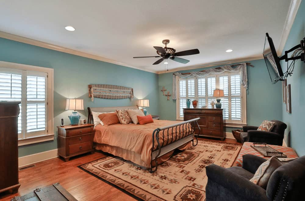 Aqua primary bedroom with a seating area and a wall-mount TV facing the metal bed that's situated in between wooden nightstands. It has hardwood flooring and glazed windows dressed in charming valance.