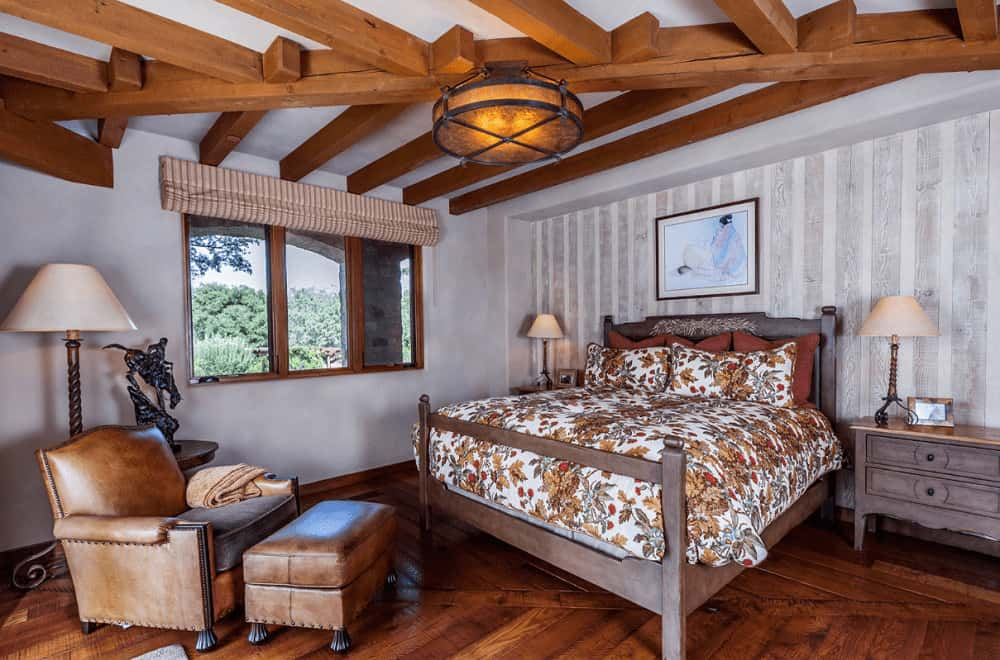 Southwestern bedroom offers a leather lounge chair and a cozy bed that complements the natural wood nightstands. It is illuminated by a warm drum flush light mounted on the stylish wood beam ceiling.