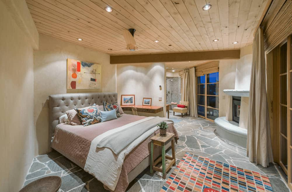 A lovely artwork hangs above the gray tufted bed in this primary bedroom with rustic wood beam ceiling and flagstone flooring topped by a multicolor checkered rug.