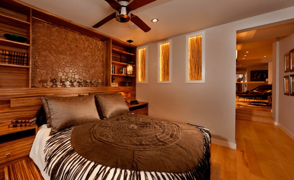 Warm primary bedroom with gorgeous inset wall niches and comfy bed wrapped in a round tasseled blanket. It has a custom wood headboard fitted with open shelving.