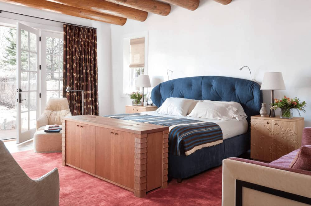 A blue tufted bed stands out in this white primary bedroom with wood beam ceiling and white French door that opens to the yard. It is accompanied by cozy seats and carved wood nightstands topped with table lamps.