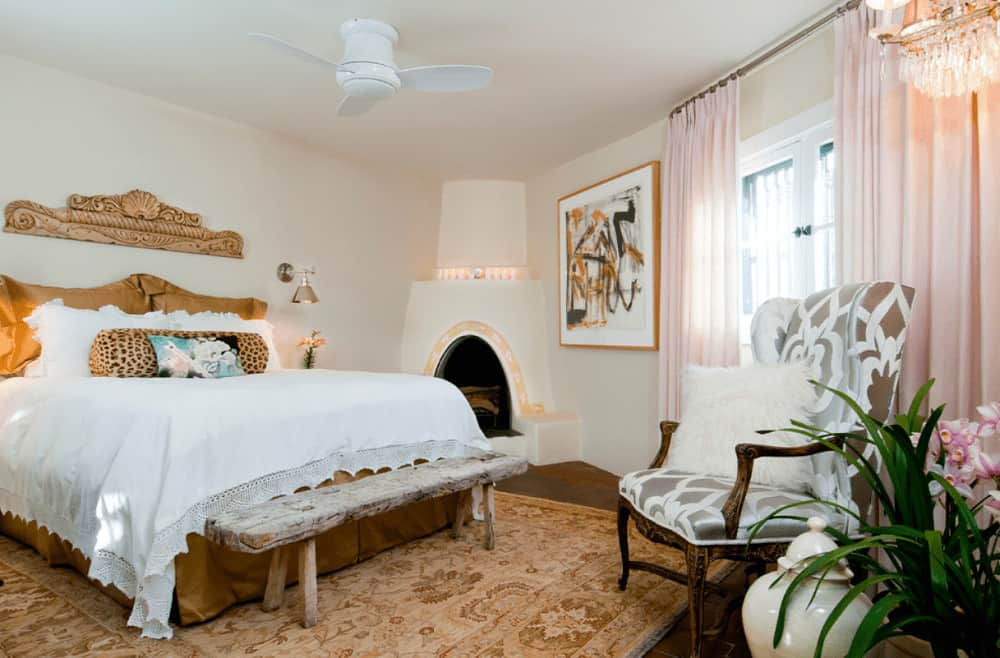 Charming bedroom boasts a corner fireplace and skirted bed accompanied by a rustic bench and patterned wingback chair that's topped with a white faux fur pillow.