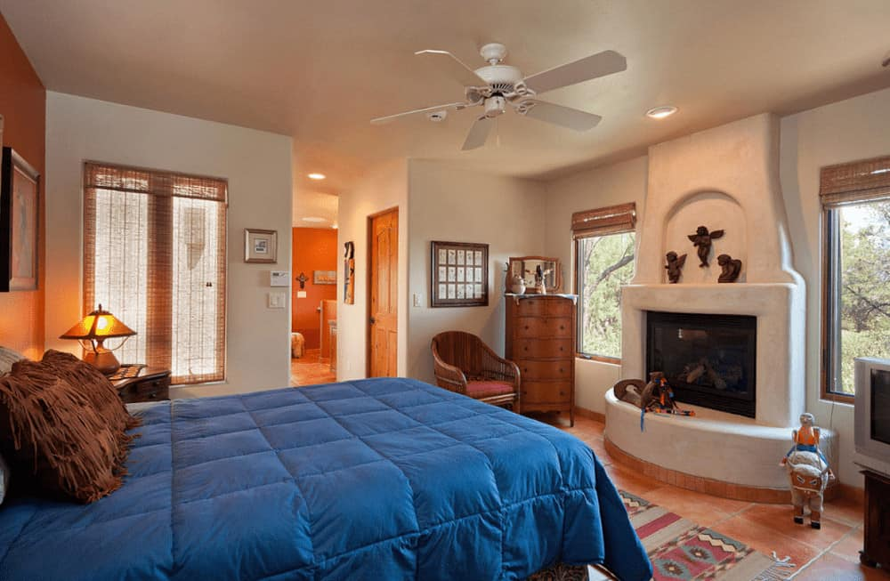 A tasseled runner lays on the terracotta flooring in this primary bedroom with a comfy bed and a white kiva fireplace decorated with small angel sculptures.