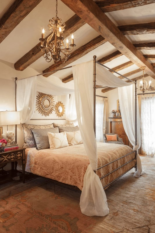 An ornate candle chandelier that hung from the wood beam ceiling illuminates this primary bedroom featuring a gorgeous canopy bed designed with sunburst mirrors.