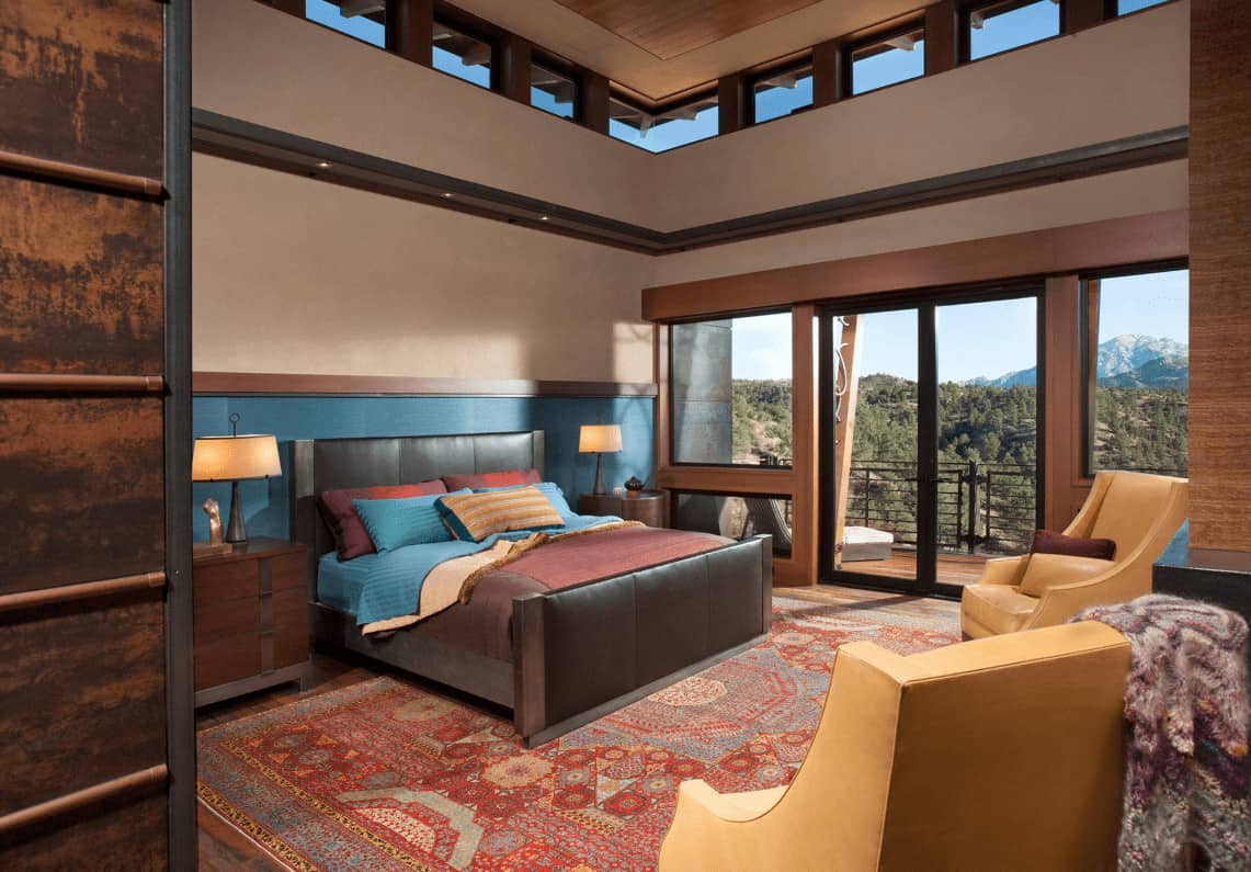 Southwestern bedroom with hardwood flooring and glass double door leading out to the balcony with a breathtaking view. It has a black leather bed and beige armchairs that sit on a classic area rug.