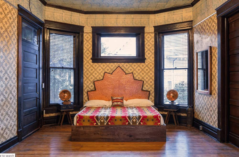 Clad in patterned wallpaper, this primary bedroom features an eye-catching bed flanked by small nightstands and vintage lamps.
