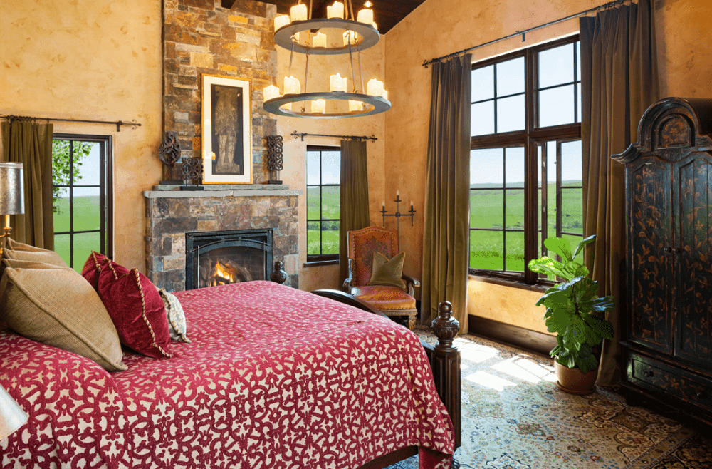 Southwestern bedroom with a two-tier candle chandelier and a stone brick fireplace topped with framed artwork and ornate decors. It includes a leather chair and a wooden bed dressed in red patterned bedding.