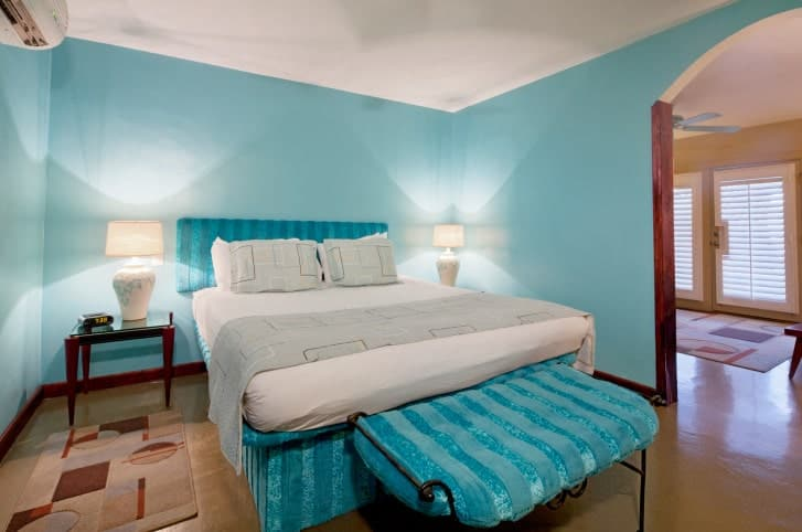 A black metal cushioned bench matches the blue striped bed in this sky blue bedroom illuminated by white table lamps that sit on wooden nightstands.