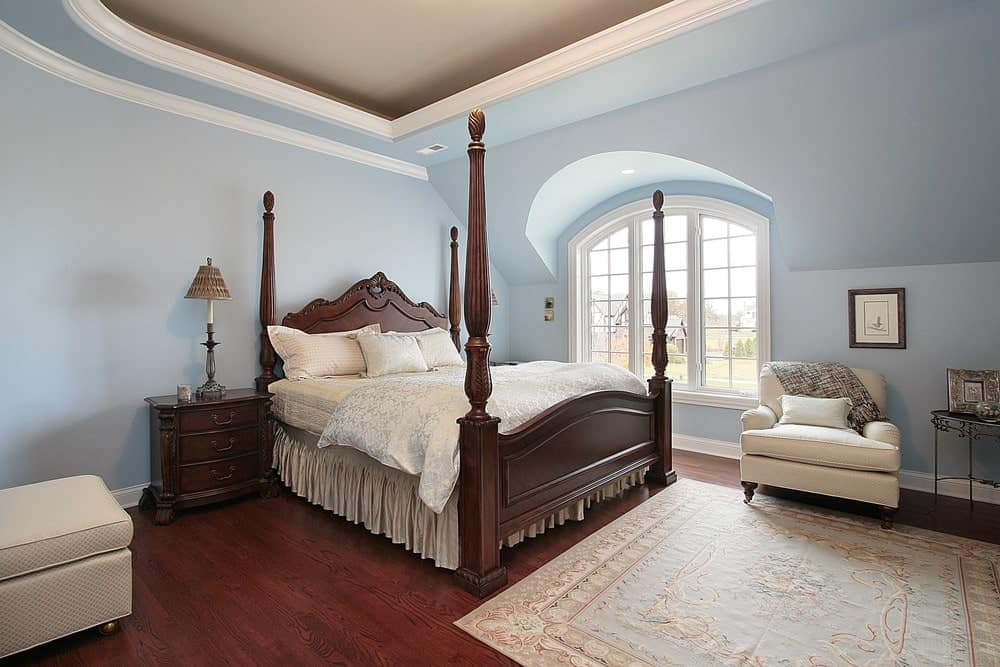 Charming primary bedroom with a tray ceiling and rich hardwood flooring topped by a light blue rug. It has beige seats and a four poster bed that complements the wooden nightstands.