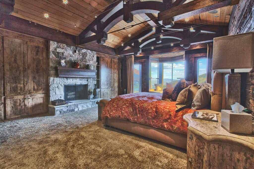 Rustic primary bedroom with wooden nightstand and a tufted bed that faces the stone brick fireplace lined with dark wood mantel. It is illuminated by track lights fixed on the wood plank ceiling.