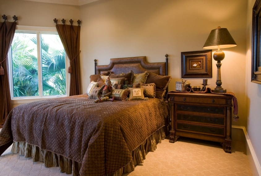 Warm bedroom with textured carpet flooring and a glazed window covered in charming brown draperies. It includes a skirted bed and wooden nightstand topped with a bronze table lamp.