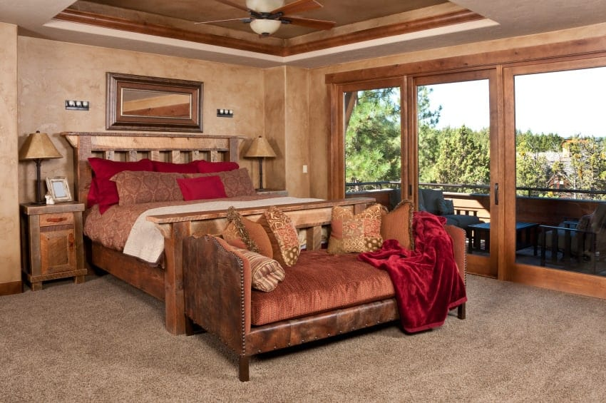 Brown primary bedroom with subtle red accents from the pillows and velvet throw blanket that lays on the cushioned bench. It has tray ceiling and glass door leading out to the balcony.