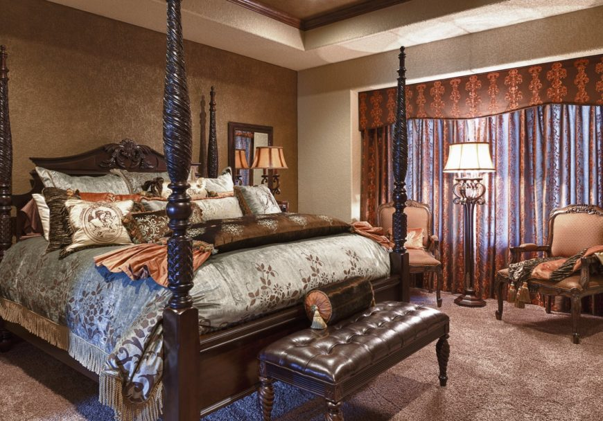 Sophisticated primary bedroom features a carved wood four poster bed accompanied by a tufted leather bench and cushioned armchairs that are lighted by a classic floor lamp.