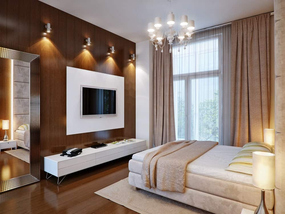 Classy bedroom showcases a gorgeous chandelier and beige velvet bed facing the wall mount TV highlighted by white track lights.