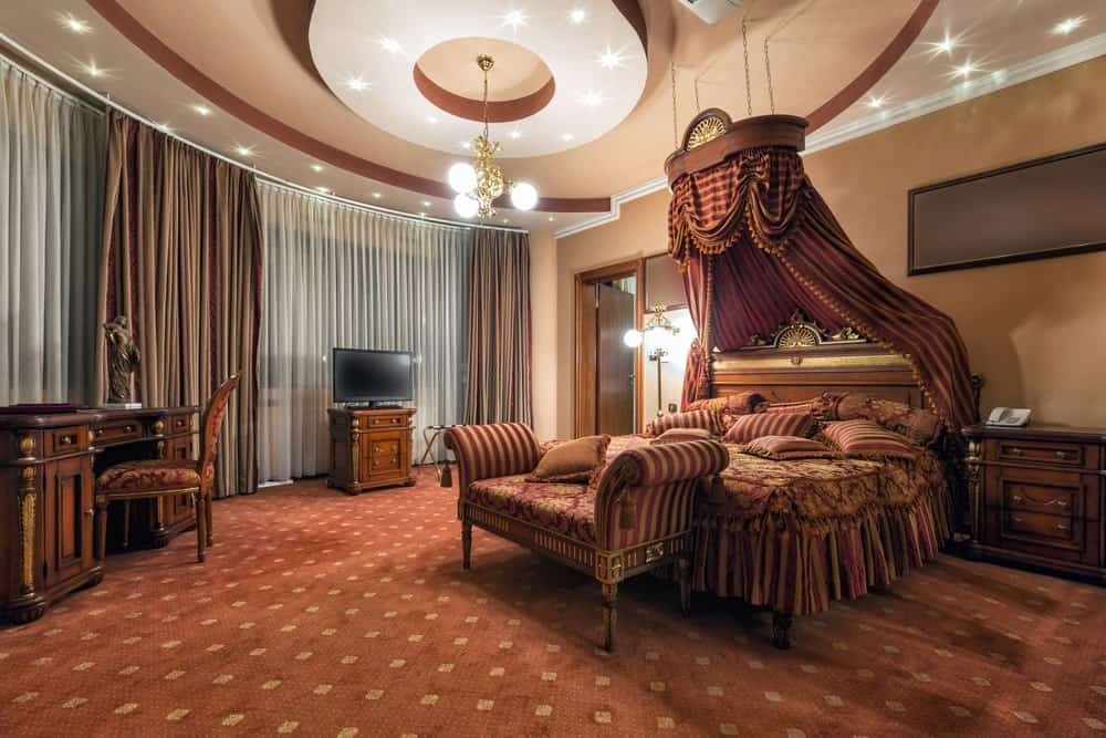 Luxury bedroom with carpet flooring and stunning tray ceiling mounted with recessed lights and a brass chandelier. It includes a wooden desk and a skirted bed with a classy canopy overhead.