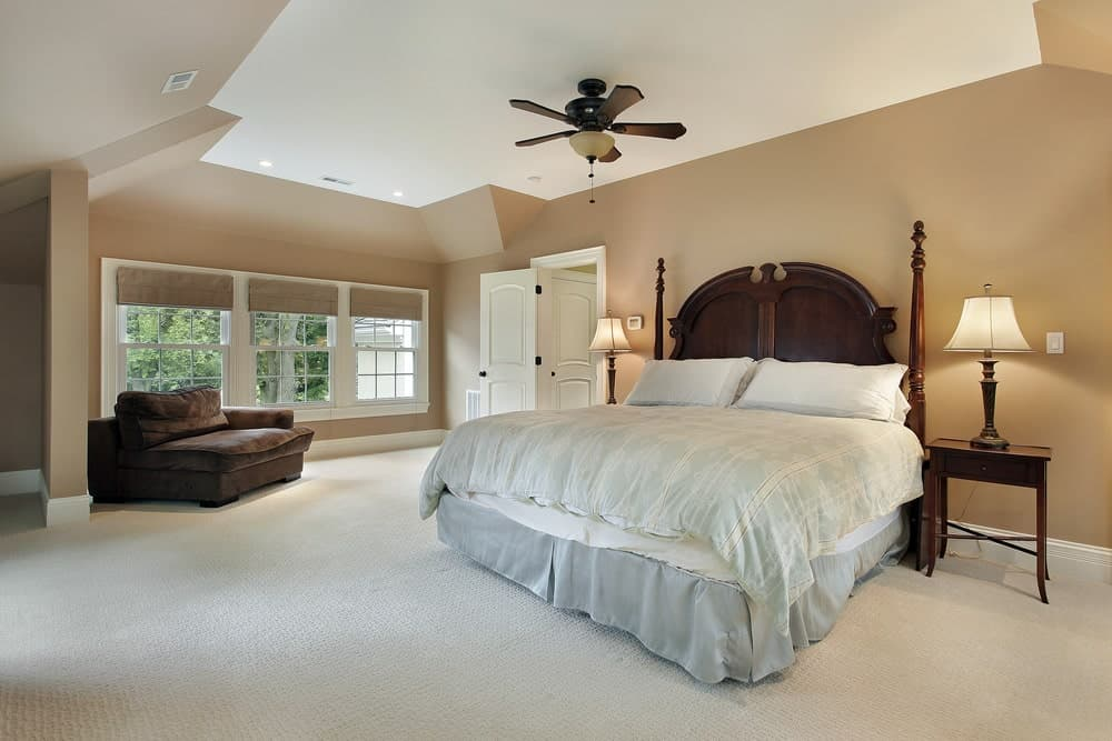 Spacious primary bedroom with brown velvet chaise lounge and a skirted bed complementing with the wooden nightstands and ceiling fan. It has carpet flooring and white framed windows that invite natural light in.