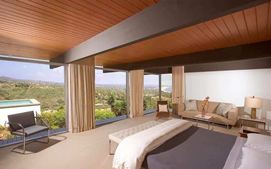The modern bedroom offers a sleek bed with white tufted bench and a seating area on the side lighted by a table lamp. It has wood beam ceiling and panoramic windows overlooking a breathtaking view.