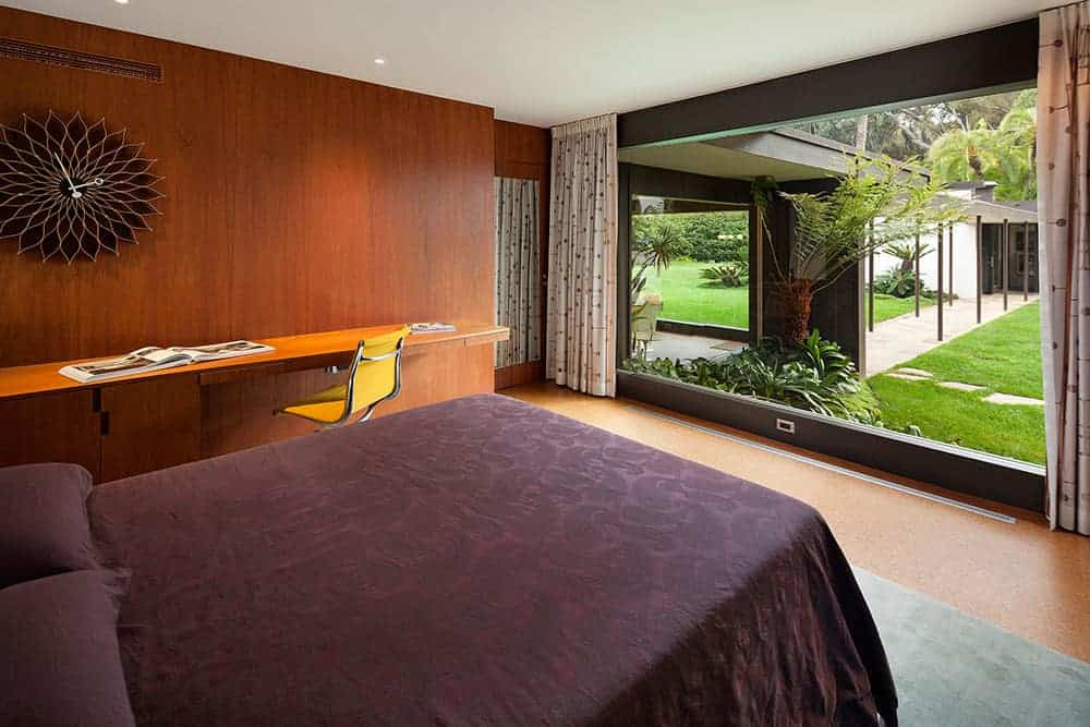 Brown primary bedroom with a comfy bed and a stylish wall clock that hung above the floating desk paired with a yellow swivel chair. It has wood paneled walls and a panoramic window overlooking the lush green garden.