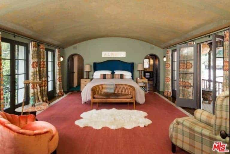 Mediterranean primary bedroom with a large area rug covering the hardwood flooring. The room offers a classy bed along with the doorway leading to the home's terrace.